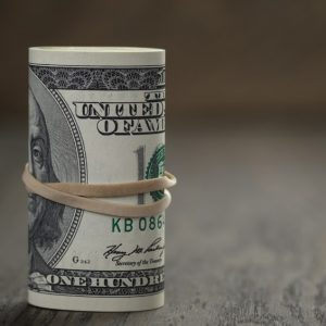 roll of old style hundred dollar bills stand on wooden table, Shallow DOF